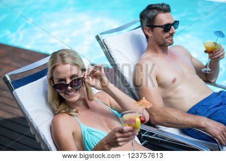 Couple lying on sun lounger and having cocktail near pool