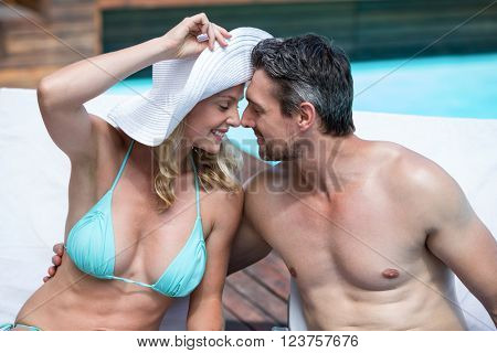 Portrait of happy couple sitting on sun lounger and embracing near the pool