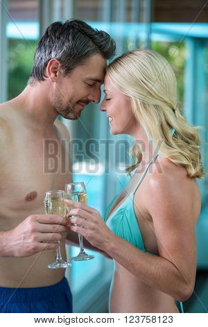Couple holding a champagne glass while romancing near the pool