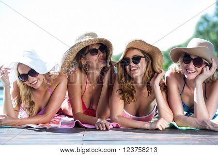 Group of happy friends lying near pool on a sunny day