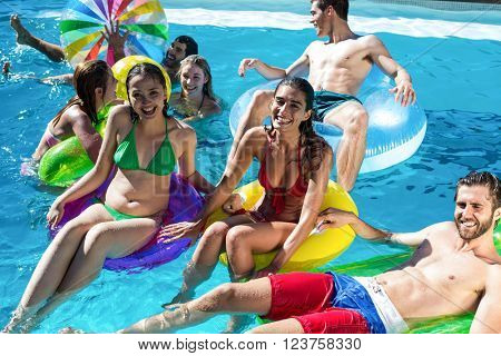 Group of friends having fun in swimming pool on a sunny day