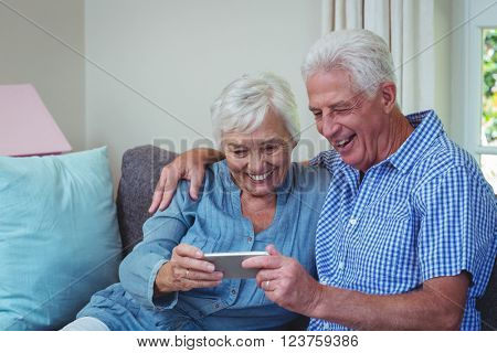 Happy senior couple using phone at home