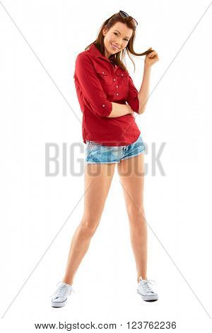 Attractive young woman in jeans shorts and red shirt, summer clothes, isolated over white background