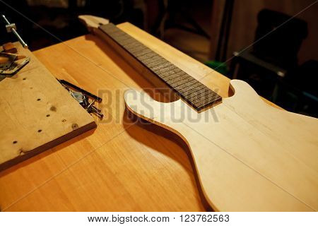 Billet of wood for bass guitar. Manufacture and repair of musical instruments. Installing the guitar frets.
