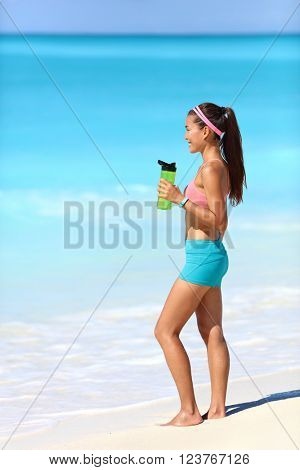 Beach runner woman taking running break drinking water standing on white sand. Healthy fit girl wearing smartwatch activity tracker bracelet holding bottle for hydration during exercise.