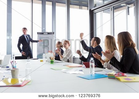 Business man showing ground-plan during meeting in modern office while his colleagues cheering.