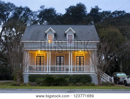 Front elevation of house lit up at twilight