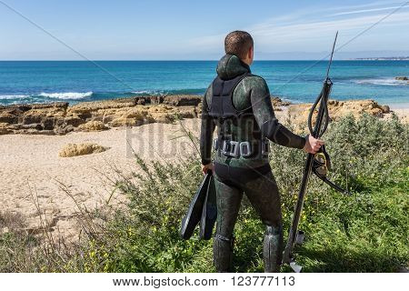 Underwater hunter with a gun in a mask.  Looking at the sea.