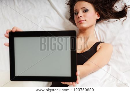 Sexy lazy girl in body underwear showing copy space on tablet touchpad on bed. Woman relaxing lazing in bedroom. Technology.