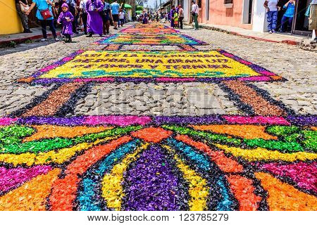 Antigua Guatemala - March 24 2016: Locals walk past handmade dyed sawdust Holy Thursday carpets for procession in colonial town with most famous Holy Week celebrations in Latin America.