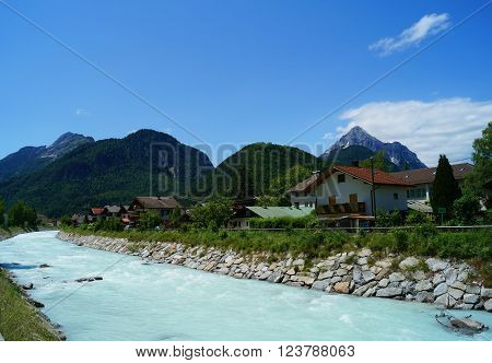 Milky white turquoise turbulent mountain river channelled through the German city Mittenwald at the foothills of the Alps.