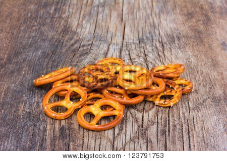 a handful of small pretzels on an old wooden table in the cracks. selective focus