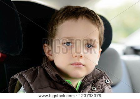 Sad Little Boy In Car Safety Seat.