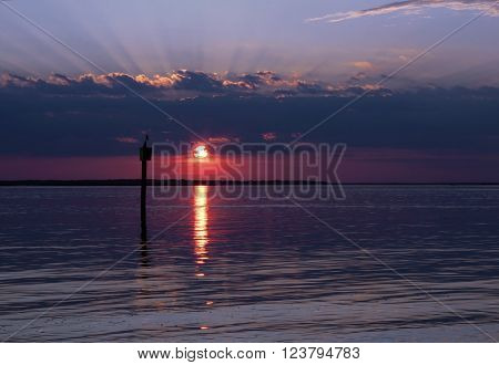 Sunset over the waters around Jekyll Island, Georgia as the rays of the setting sun burst above a cloud bank over the horizon poster