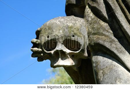 Skull with hand (part of a stone sculpture)