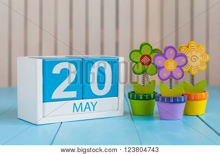 May 20th. Image of may 20 wooden color calendar on white background with flower. Spring day, empty space for text. World Metrology Day.
