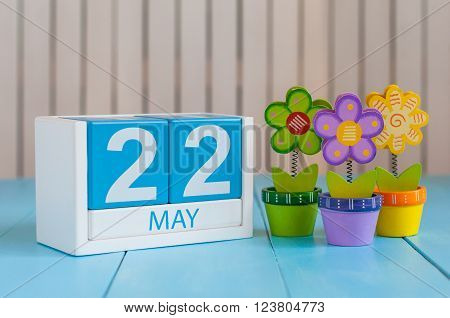 May 22nd. Image of may 22 wooden color calendar on white background with flower. Spring day, empty space for text.