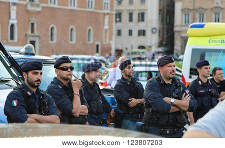 Rome, Italy - June 25, 2014: A group of armed police officers standing near the police car on one of the main streets of Rome during a public event. Police are closely monitoring what is happening around.