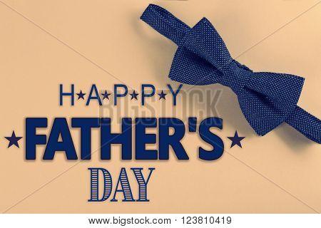 Happy Father's Day. Dark blue bow tie on beige background