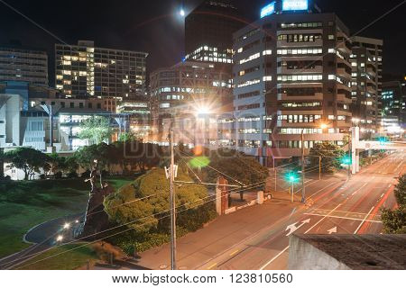 Wellington, New Zealand - February 15, 2016; Hectic night scene of buildings streets lights tram lines and power poles across Jervois Road with The Rugby World Cup Celebration sculpture in small park Wellington New Zealand