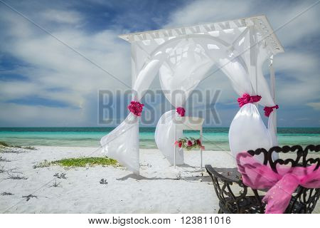 Stunning, splendid gorgeous view of wedding decorated gazebo on Cuban Cayo Coco tropical beach against tranquil turquoise ocean and dark blue beautiful sky background