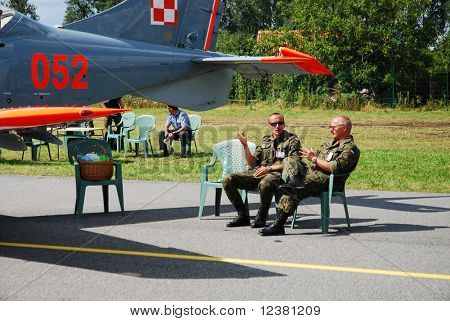 RADOM, POLAND - AUG. 31: Two pilots sitting next to the aircraft Orlik. International Air Demonstrations AIR SHOW 2009. August 31, 2009 in Radom, Poland.