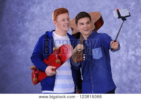 Two teenager boys with guitar and skateboard using stick for photo by their self on grey background