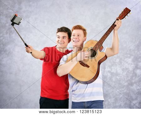 Two teenager boys with guitar using stick for photo by their self on grey background