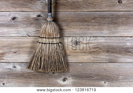 Old straw broom on stressed wooden floor.