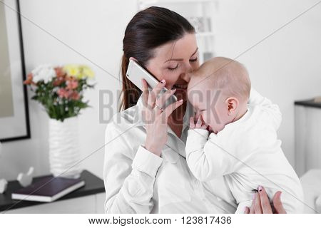 Businesswoman with baby boy working from home using mobile phone