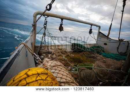 Fishing nets are on the deck of a small fishing vessel. In the Sea of Japan in the evening.