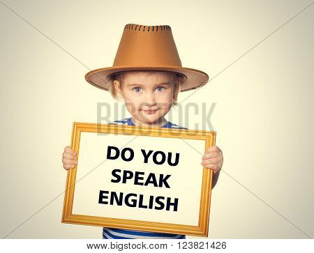 Little Funny girl in striped shirt with blackboard. Text do you speak english.  Isolated on gray background