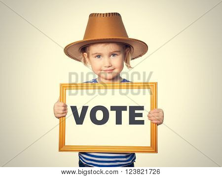 Little Funny girl in striped shirt with blackboard. Text VOTE.  Isolated on gray background.