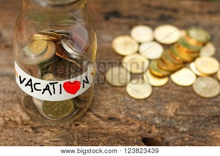 A glass jar labeled vacation filled with money