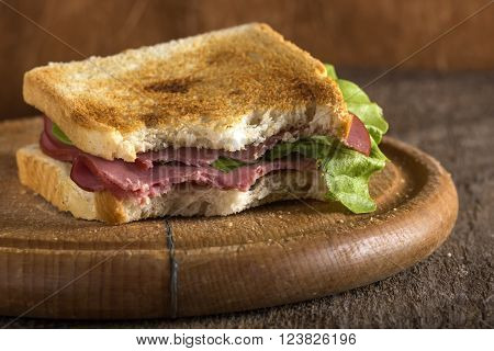 Bitten beef pastrami sandwich with lettuce and tomato over wooden background