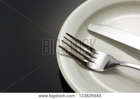 knife and fork at plate on black background