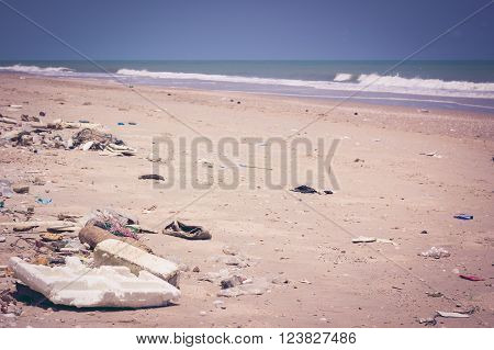 Pollution on the beach of tropical sea. Plastic garbage, foam, rubbish and dirty waste on beach in summer day. The sky above is a perfect blue color. Outdoors. Vintage picture style.