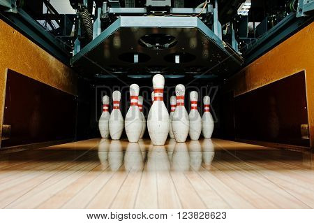 Ten White Pins In A Bowling Alley Lane