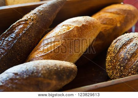 food, baking, junk-food and unhealthy eating concept - close up of bread loafs at bakery