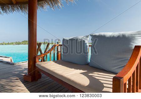 travel, tourism, vacation and summer holidays concept - patio or terrace with canopy and bench on beach