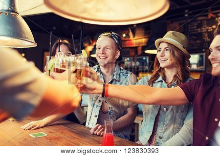 people, leisure, celebration and party concept - group of happy smiling friends clinking glasses with drinks at bar or pub