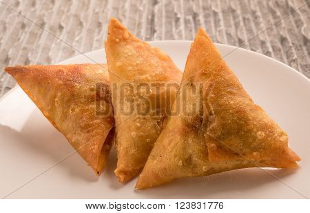 Samosas a spicy blend of vegetables or meat wrapped in a deep fried triangular pastry parcelSamosas a spicy blend of vegetables or meat wrapped in a deep fried triangular pastry parcel