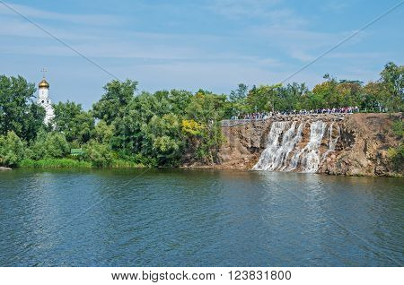 Dnepropetrovsk Ukraine - September 14 2013: View of the green river island with church and waterfall on a clear sunny day