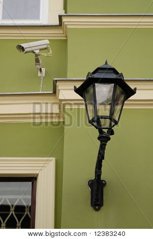 Old street light on a green brick wall.