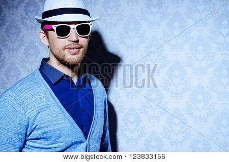 Men's beauty, fashion. Elegant good looking young man in a hat.