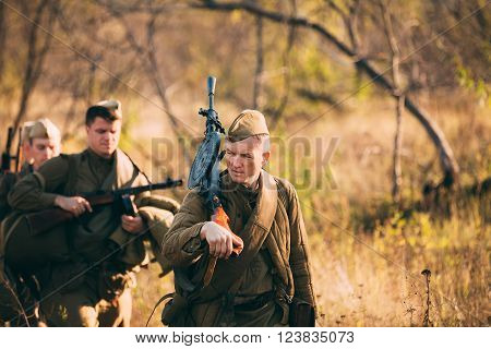 Teryuha, Belarus - October 3, 2015: Unidentified re-enactor dressed as World War II Soviet russian soldier with machine gun in his hand walking through forest.