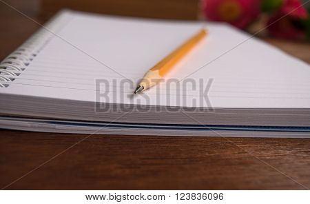 Notebooks and pencil on wooden background camelia ** Note: Shallow depth of field