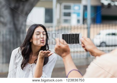 Man photographing woman blowing kiss in city