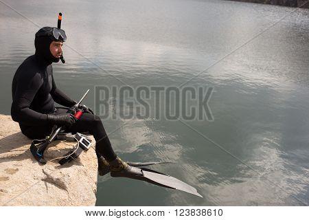 Man dressed as a hunter with an underwater scuba gun.
