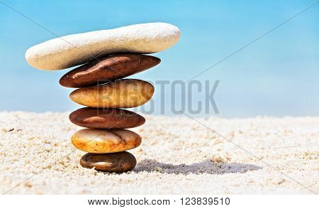 Six white and brown stones are on sandy beach